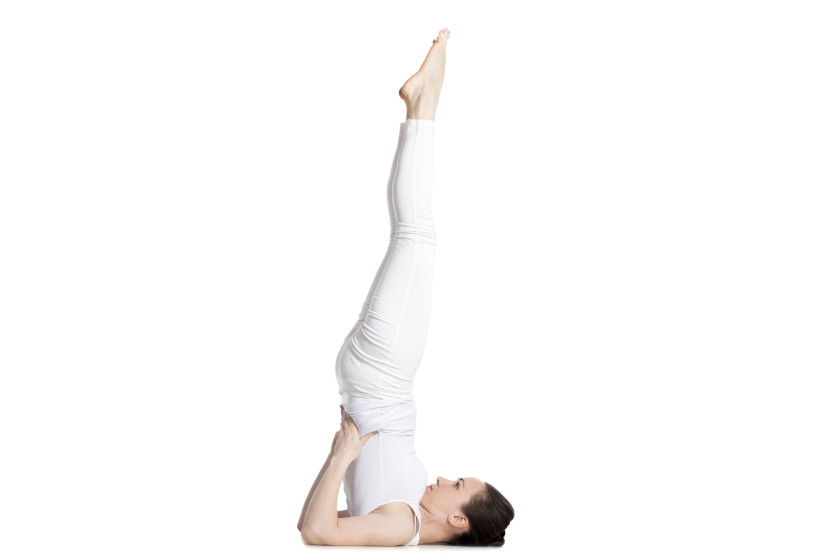 Sporty beautiful young woman in white sportswear doing Supported Shoulderstand exercise, Salamba Sarvangasana, studio full length isolated shot, side view